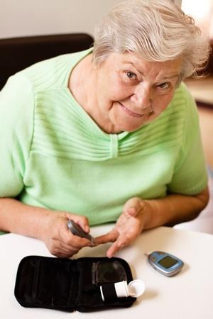 diabetes needles: old woman in blood sugar measure