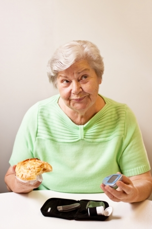 old woman with bun and blood glucose meter Stock Photo - 14407487