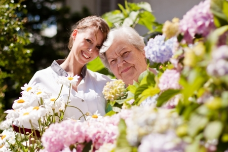 care at home: geriatric nurse with senior woman in the garden