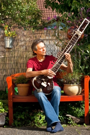 overtone: older man is playing a sitar