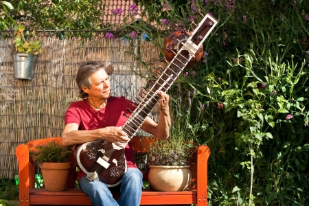 overtone: relaxed man sitting in his garden and playing sitar