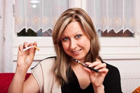 cigarette smoke: Bionda bella donna sceglie una sigaretta elettronica e distrugge il normale