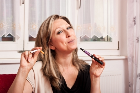 Pretty woman opts for an electronic cigarette and destroys the normal Stock Photo