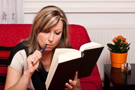 Young blonde woman reading a book, and evaporated to an electric cigarette photo