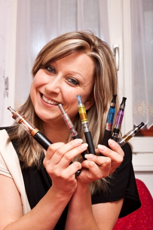 Young pretty woman shows multiple e-cigarettes and smiles photo