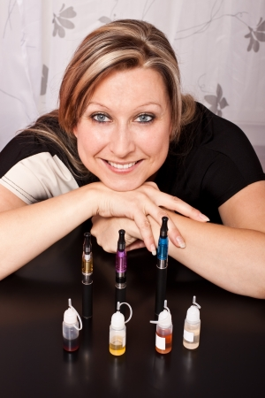 Blonde pretty girl shows her collection of e-cigarettes and various liquids
