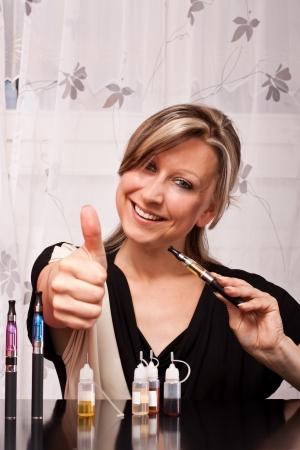 Jonge blonde vrouw met sigaret elektrische apparatuur heft duim omhoog