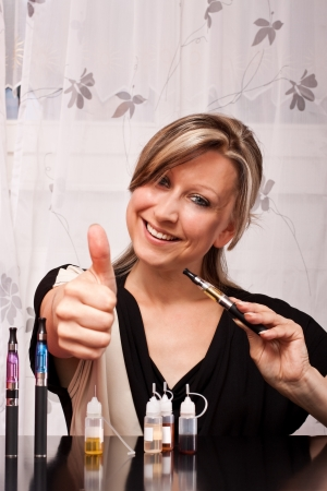 Young blonde woman with cigarette electrical equipment  lifts thumb up photo