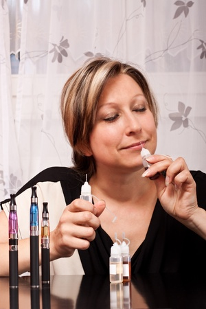 liquid reflect: Young blonde woman tests the scent of their liquid flavorings for the e cigarette Stock Photo