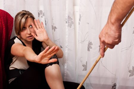 Blonde woman sitting in the corner, looking anxiously at a perpetrator of violence photo