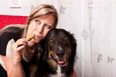 pretty blonde woman with mixed breed dog evaporated E Cigarette photo