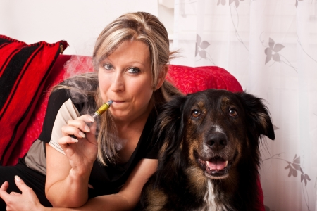 Blonde woman with a dog smoking a e cigarette photo
