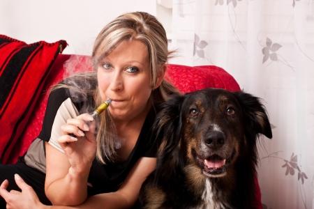e cigarette: Blonde woman with a dog smoking a e cigarette