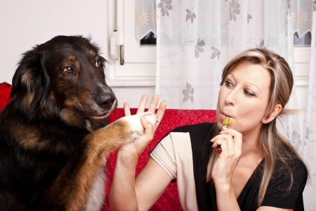 Blonde cute woman give dog high Five and evaporated electric cigarette photo