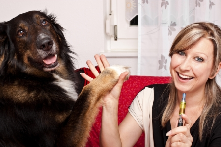 Blonde woman give dog high Five and evaporated electric cigarette