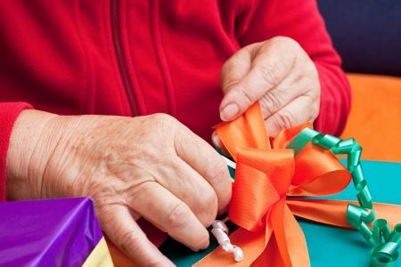 uitpakken: vrouwelijke senior wikkel of uitpakken geschenken, close-up