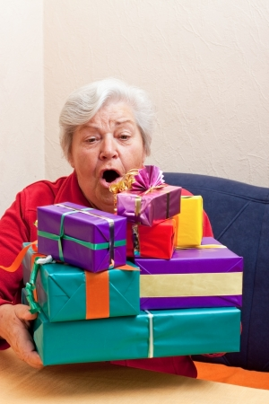 recieve: senior sitting on the couch and takes or gives gifts stack