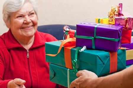 a female Senior sits and gets or give many gifts photo