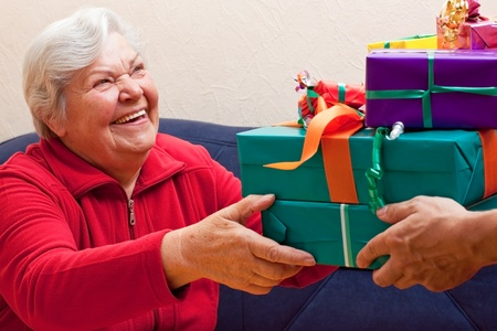 a female Senior sits and gets or give many presents photo
