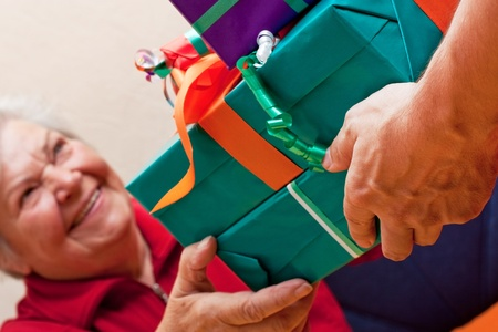 a female Senior sits and gets or give many presents closeup photo