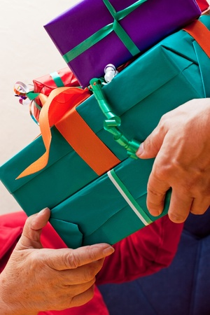 a female Senior sits and gets or give many gifts closeup photo