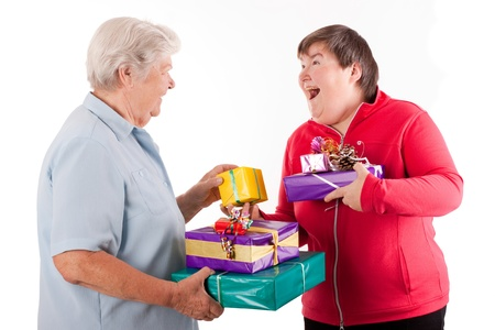 mentally: female senior and mental disabled woman holding presents