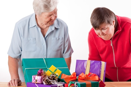 mentally: Senior with mentally handicapped woman consider presents
