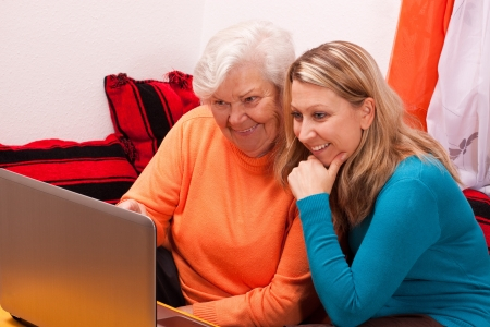 old pc: young female shows an senior how to use internet