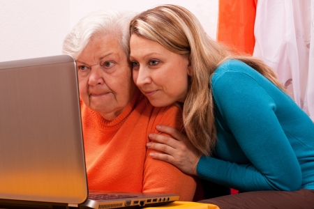 technically: young female shows an senior how to use modern technology
