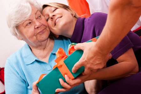 gives: old woman gets a gift, young woman is happy about