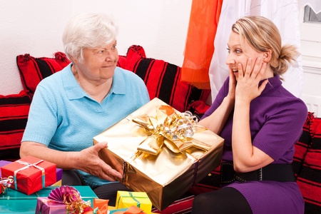 gives: female senior gives present to young blonde woman