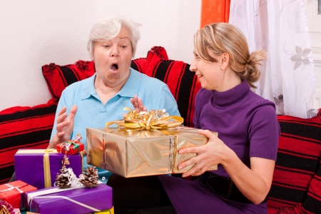 gives: female senior gets a present from a pretty young Stock Photo