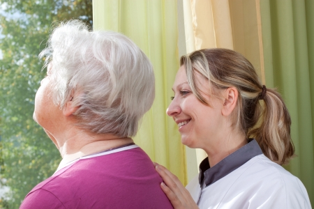 female nurse and elderly woman standing at the window photo
