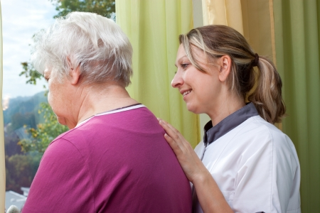 Nurse and old woman standing at the window photo