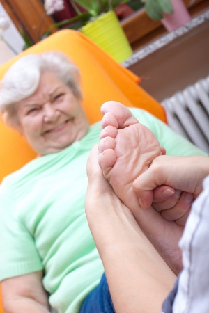 wellbeeing: female Nurse massaging foot of an elderly woman
