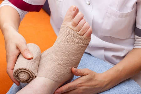 female Doctor bandaged foot of a patient Stock Photo
