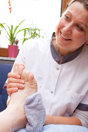manos y pies: Enfermera lava los pies de un paciente de edad avanzada Foto de archivo
