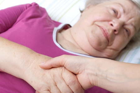 Elderly woman lying in bed and welcomes nurse Stock Photo - 15812345