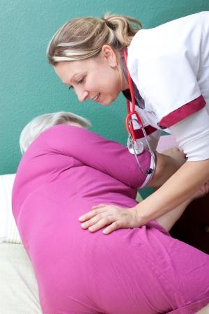 get up: female Nurse helps patient to get up
