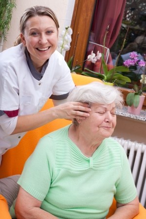 female Nurse massages the head of a senior photo