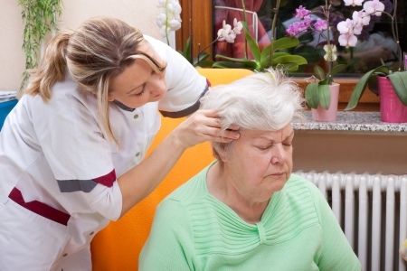 head home: female Nurse massages the head of a senior Stock Photo