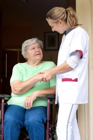 d?a: Enfermera y paciente mayor en silla de ruedas le da un apret�n de manos entre s�