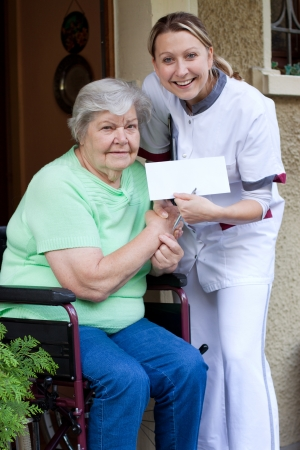 female Nurse and senior patient in a invalid chair gives each other a handshake Stock Photo - 15812362