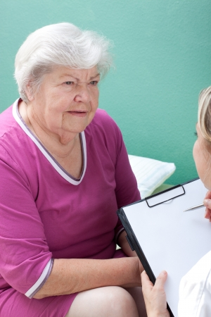 female senior with doctor and clipboard Stock Photo - 15812356