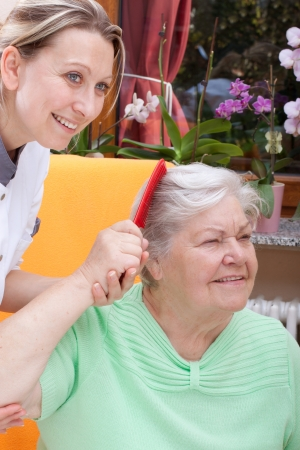 female Nurse combs the hair of a senior citizen