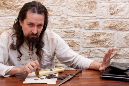 medieval dressed man prefers tradition instead of technology photo