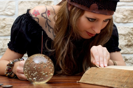 suggests: Fortune teller reads a book and suggests the future Stock Photo