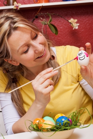 blond woman paints an egg with funny face