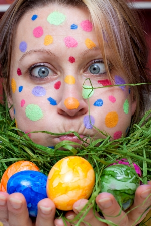 woman with colorful points in the face and easter eggs in her hands
