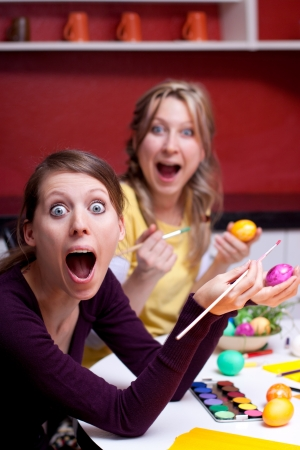 Two pretty young women with Easter eggs look surprised photo
